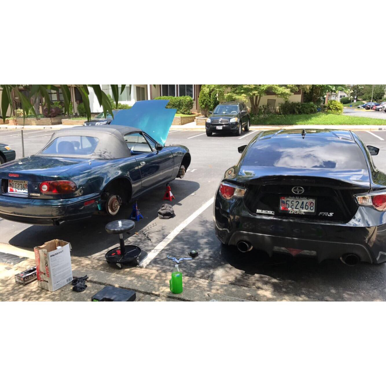 FRS, next to Miata, Lifted on jack stands.